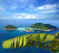 Two tropical islands at ocean through banana leaf Royalty Free Stock Photo