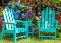 Two turquoise Adirondack chairs and a matching table surrounded by beautiful flowers and trees and shining mirror balls handing fr
