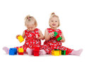 Two twin girls in red dresses playing with blocks children and twins concept identical toy Stock Images