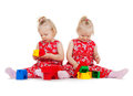 Two twin girls in red dresses playing with blocks children and twins concept identical toy Royalty Free Stock Photo