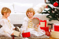 Two twins girl opening gifts near Christmas tree Royalty Free Stock Photos