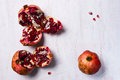 Two uncovered and a one whole pomegranates on the white table Royalty Free Stock Photo