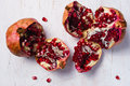 Two uncovered pomegranates on the white table Royalty Free Stock Photo