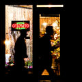 Two unknown men go in the dark by flower shop with the shining plate openly Stock Images