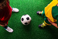 Two unrecognizable little football players against green grass Royalty Free Stock Photo