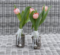 Two vases with pink tulip flowers and heart shapes for mothers day on bamboo background Stock Photography
