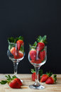 Two vine glasses filled with fresh strawberry on wooden table Royalty Free Stock Photo