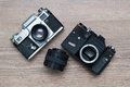 Two vintage photo camera and lens on a wooden background Stock Photography