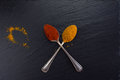 Two vintage spoons with spices curry and paprika on black background. Royalty Free Stock Photo