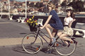 Two vintage women on bicycle near the sea couple of fashion with style colourful tulips in basket of bike in color outdoor Royalty Free Stock Photo