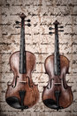 Two violins on an antique texture background Royalty Free Stock Images