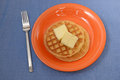 Two waffles for breakfast on orange plate and bright blue background Stock Photography