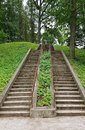 Two walking paths to the top of the hill with steps in a green park Royalty Free Stock Photo
