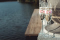 Two wedding champagne glasses with a bow on a stone railing. Lake promenade at sunset Royalty Free Stock Photo