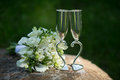 Two wedding glasses and bridal bouquet on stone in summer garden Royalty Free Stock Photography