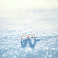 Two wedding gold rings on the snow in winter day Royalty Free Stock Photo