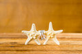 Two wedding rings with two starfish on wooden table Royalty Free Stock Photo