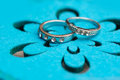 Two wedding rings white gold on a turquoise background Royalty Free Stock Photo