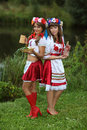 Two well dressed girls in ukrainian costumes on the banks of the river with vodka and light meal up for the holiday of ivan kupala Stock Photography
