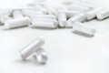 Two white capsules and heap of capsules on white background.