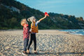 two white Caucasian children kids, older sister and younger brother playing paper planes on ocean sea beach on sunset outdoors Royalty Free Stock Photo