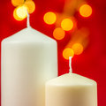 Two white christmas wax candles on red background Royalty Free Stock Photo