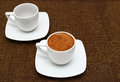 Two white cups with greek coffee on a sacking background dark Stock Image