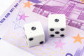 Two white dices with black dots are laying on 500 euro banknote Royalty Free Stock Photo