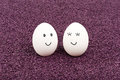 Two white eggs on purple sand smile at each other Royalty Free Stock Images