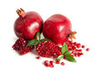Two whole and part of a pomegranate with pomegranate seeds Royalty Free Stock Photo