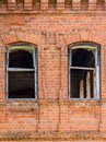 Two windows of an old destroyed building made of red brick, through which you can see the dark ruined rooms. Royalty Free Stock Photo