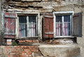 Two windows in the ruin of a house weathered with shutters and curtains an abandoned Royalty Free Stock Photos