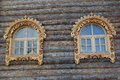 Two windows with wooden carved platbands on a timbered wall Royalty Free Stock Images
