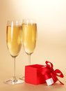 Two wine glasses with champagne and gift a small box an open cover on a beige background Stock Photography