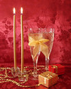 Two wine glasses with champagne, gifts and golden candles on red Royalty Free Stock Photography