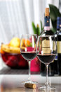 Two wine glasses filled still life composition with of on a white table cork in the background out of focus a few bottles of and Royalty Free Stock Photography