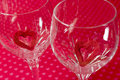 Two wine glasses with red felt cutout hearts inside, soft floral