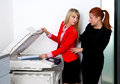 Two woman colleagues working on printer in office attractive women business and chatting Stock Photography