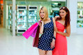 Two woman friends in shopping mall with bags Royalty Free Stock Photo