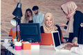 Two woman with hijab working on laptop in office. Royalty Free Stock Photo
