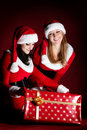 Two woman in Santa costume opening christmas gift. Royalty Free Stock Photo