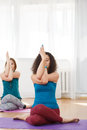Two woman showing asana is gomukhasana with eagle arms indoor Royalty Free Stock Photo