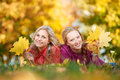 Two women at autumn outdoors smiling young attractive with maple leaves in park fall Stock Images