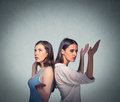 Two women back to back putting hands in air looking up in frustration Royalty Free Stock Photo