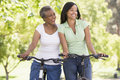 Two women on bikes outdoors smiling Stock Image