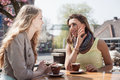 Two women in a cafe girl friends talk and drink coffee outdoors Stock Images