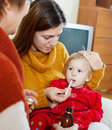 Two women caring for unwell baby at home Royalty Free Stock Photography