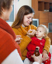 Two women caring for unwell toddler at home Stock Photos