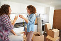 Two women celebrating moving into new home with champagne looking at each other smiling Stock Photography