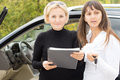 Two women checking a contract or paperwork before finalising the deal on the purchase of new car Stock Photos